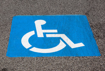 Disability symbol painted on the floor at parking lot