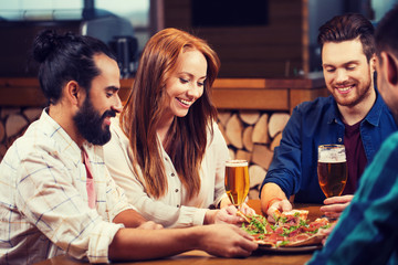 friends sharing pizza with beer at pizzeria