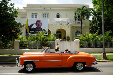 Tourists ride in a vintage car as it passes in front of a picture of Venezuela's late president Hugo Chavez hung at the Venezuelan embassy in Havana