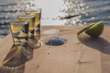 Three shots of tequila with salt and lime by the sea