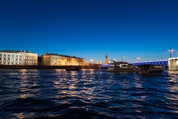 Yachts near palace bridge and Vasilievsky Island at night in St. Petersburg, Russia