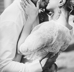 stylish wedding bride and groom kissing in sunny park, sensual moment. modern couple hugging and embracing. fine art wedding photo, romantic tender kiss close up
