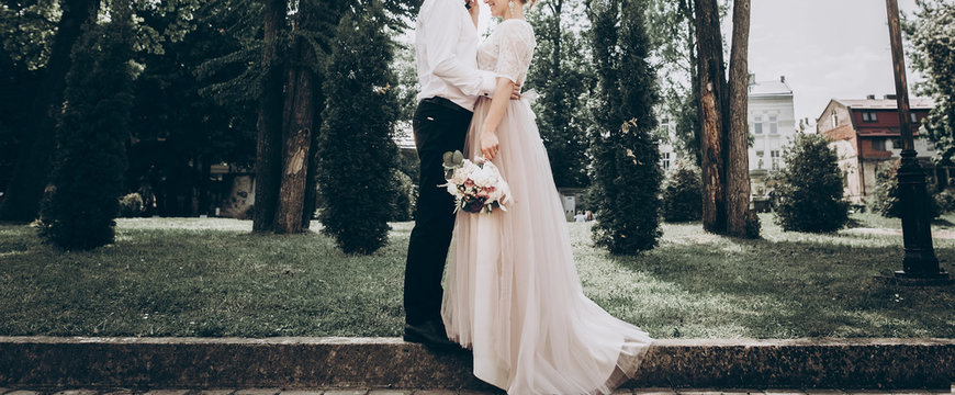 stylish wedding bride and groom in sunny park, sensual moment. modern couple hugging and embracing in garden in light. fine art wedding photo, romantic tender moment, long edge