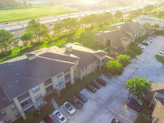 Aerial view multi-floor apartment buildings complex near highway in Humble, Texas, US. Top view garage with covered parking lots, cars and green trees. Urban infrastructure and transportation concept.