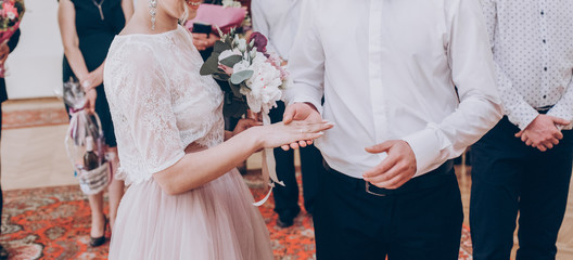 stylish wedding bride and groom exchanging wedding rings.modern couple putting on each other wedding rings. romantic tender moment, official wedding ceremony