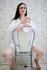 Portrait of a pretty young woman in male shirt and underwearsitting with a glass of water in her hands.
