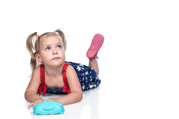 Portrait of a small beautiful girl in a dress lying on the floor and looking up, isolated on a white background