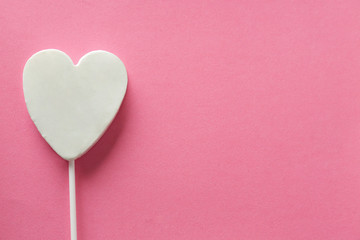 Tasty candy in shape of heart on color background