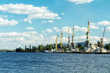 Container cranes in Dnieper river harbor. Loading and unloading cranes in the river port. The river port accepts and ships the cargo across the water.
