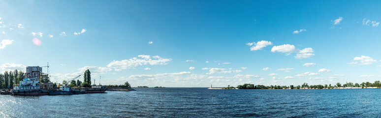 The water area in Dnieper river harbor.Old ships in the port. Breakwater and lighthouse. Panorama.