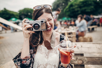 happy hipster woman in sunglasses making photo with old camera and drinking lemonade. stylish boho girl holding cocktail and smiling at street food festival. summertime