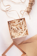 Gift packing process with craft box, twine and brown paper, top view