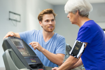 personal trainer explaining treadmill controls to seniro woman