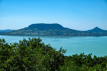 sailboat on water, greenery in foreground fameus Badacsony hill in background - summertime and vacation at Balaton lake