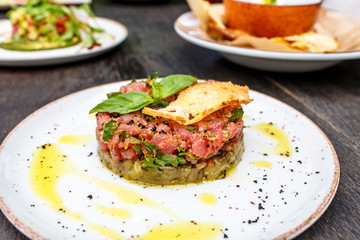 Tuna tartare with vegetables lies on plate.