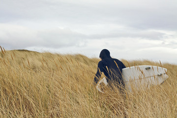 A surfers walking through the high grass of the dunes searching for waves