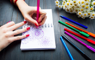 Female drawing flower shapes in notebook