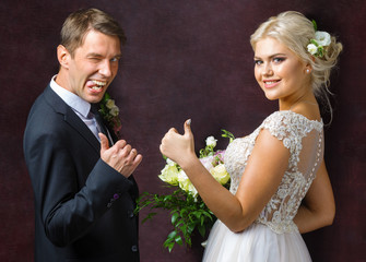 the bride and groom show a gesture of good luck and a joke