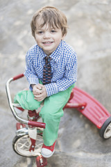 Dapper Toddler Boy On His Tricycle