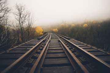 old wooden railway tracks with beautiful yellow Fall trees and fog in the distance