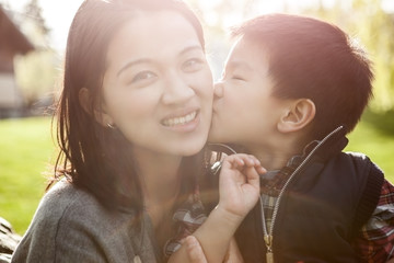 Asian boy kissing his mother