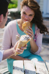 A young man holds ice cream cone while young woman smiles holding her ice cream in the background.