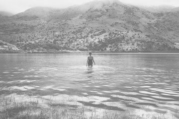 Young woman swimming in a mountain lake