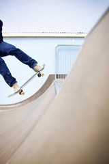 Young man landing a skateboard trick in a skate park on a sunny day