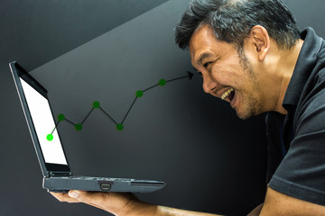 Asian man and computer stock market graph growth