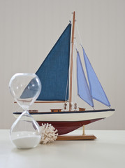 Coastal still life with sailboat and hourglass