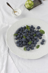 Blueberries with sugar, lime zest and mint leaves