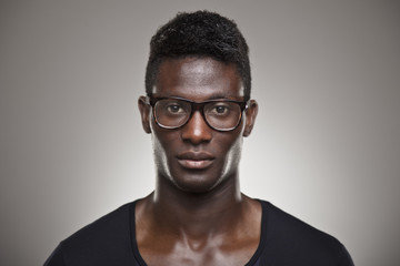 African young real man with glasses over grey background
