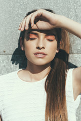 Sunlit portrait of a young woman with closed eyes