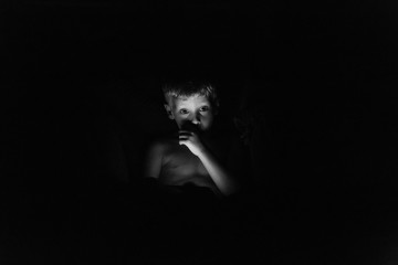 Boy with iPad in the Dark