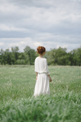 Beautiful young redhead  woman standing in a field in a white dress