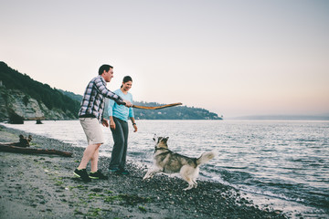 Couple playing with their dog on the beach