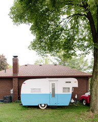 vintage camper parked by house
