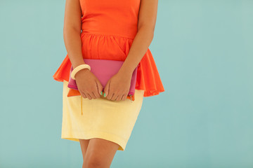Woman in an orange shirt and yellow skirt standing against blue wall.