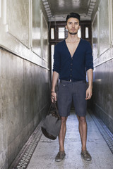 Young Man in Cardigan and Shorts Standing in Hallway