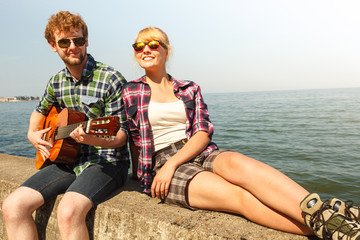 Young man hipster playing guitar for woman.