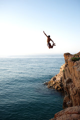 Young man jumping a cliff in a blue sea
