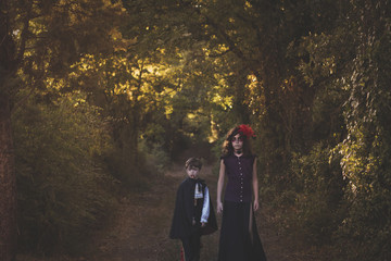 Kids wearing dracula and witch costume in a forest at Halloween