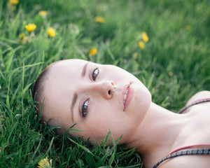 Girl lying the grass, yellow flowers