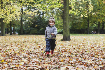 Toddler walking towards camera through leaves