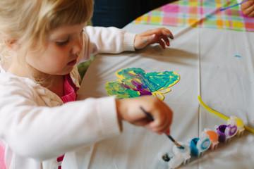 Little girl paints a butterfly.