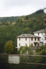 Blurred sight of building amonst treed on northern italy mountain