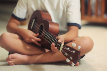 Young boy plays the Ukulele sitting on carpet