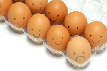 brown eggs with smile and sad face drawing