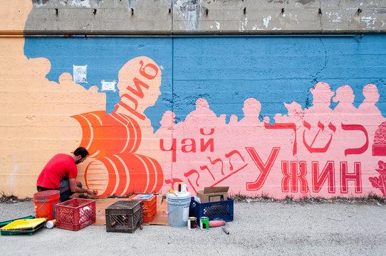 artist paints mural on a city street
