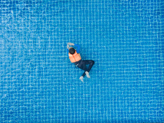 Man swim in the pool at the hotel. View from Drone.